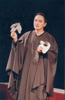 Quoc Thao as the Chorus, holding the vilains' masks of Iago and Ho Ton Hien
